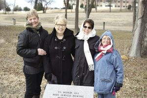 Four ladies stand around new World War I memorial