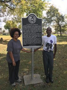 Margot Williams and Charles Cook stand next to the historic marker for Olivewood Cemetery